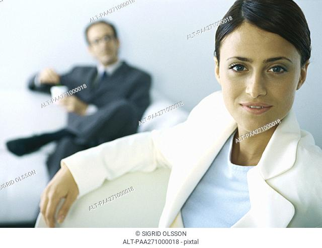 Businesswoman looking at camera, businessman with legs crosses holding cup in background