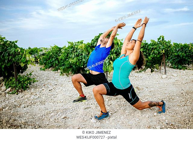 Couple doing pilates in a vineyard