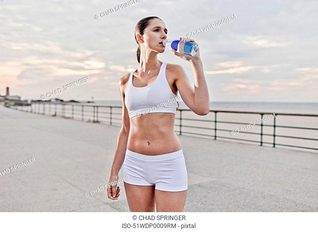 Runner drinking water at waterfront