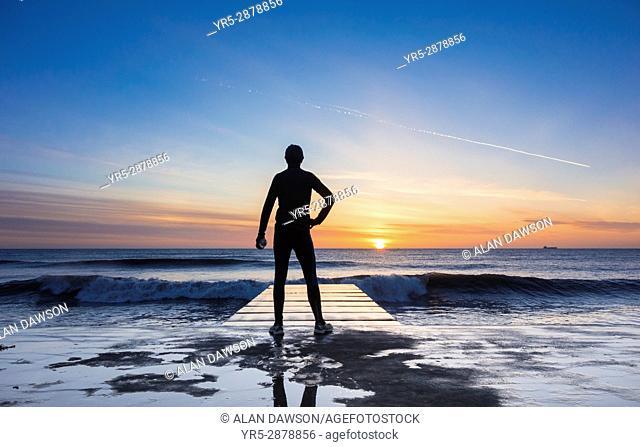 Seaton Carew, County Durham, north east England. United Kingdom. A mature jogger looks out over the North sea at sunrise