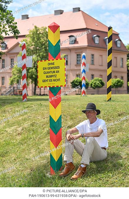 """13 June 2019, Brandenburg, Straupitz: Harald Larisch, curator of Aqaumediale, sits next to the work of art """"""""Ampel (red-yellow-green) and a saying by Theodor..."""