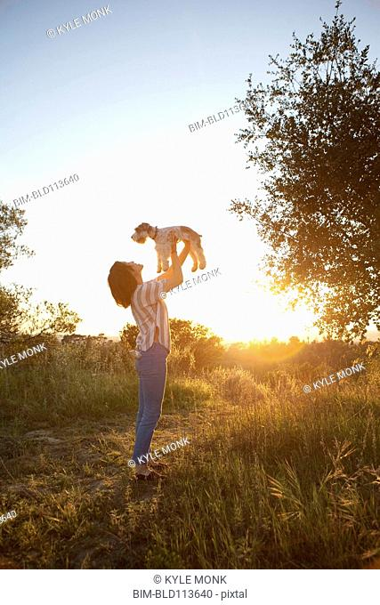 Korean woman playing with dog in meadow