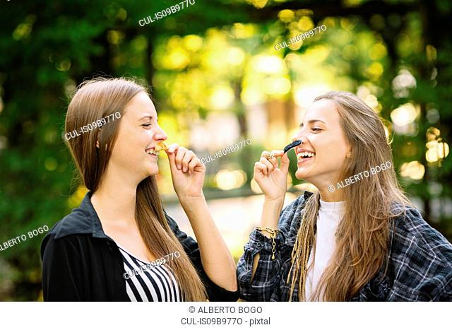 Two young female friends laughing while holding false moustache to their face in park