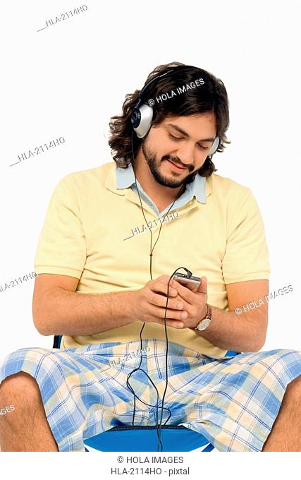 Mid adult man sitting on a stool and listening to an Mp3 player