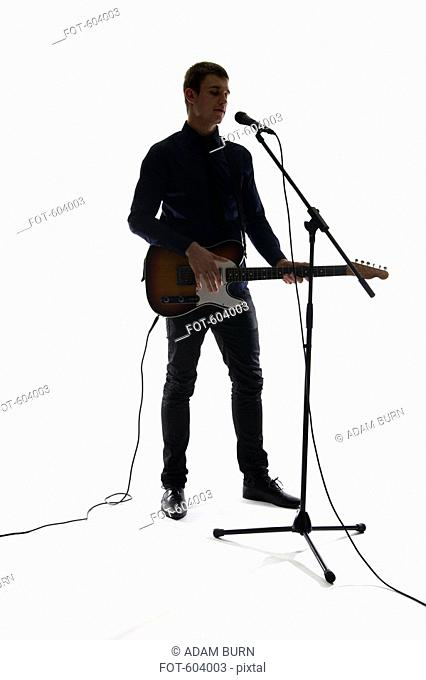 Studio shot of a man singing into a mircrophone and playing an electric guitar