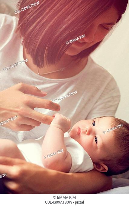 Mother holding baby's fingers
