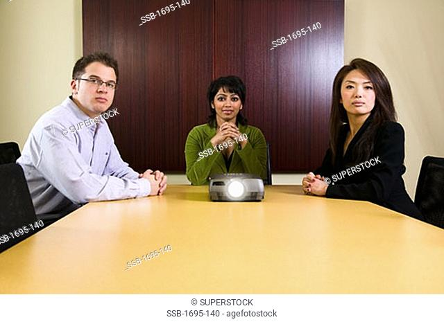 Businessman and two businesswomen sitting at a conference table