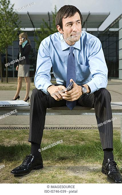 Businessman sitting on bench outdoors