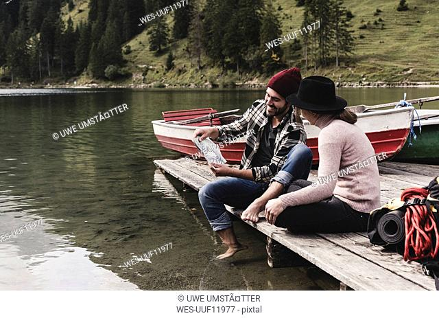 Austria, Tyrol, Alps, couple with map sitting on jetty at mountain lake