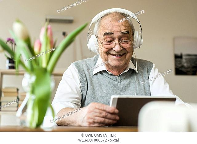 Senior man using mini tablet and headphones for skyping at home