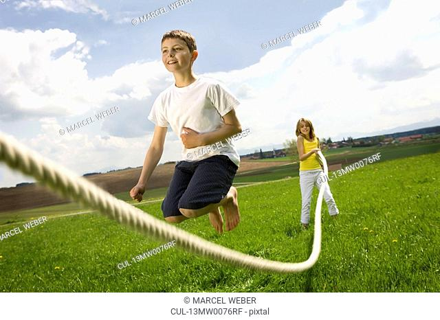 Children jump roping in countryside