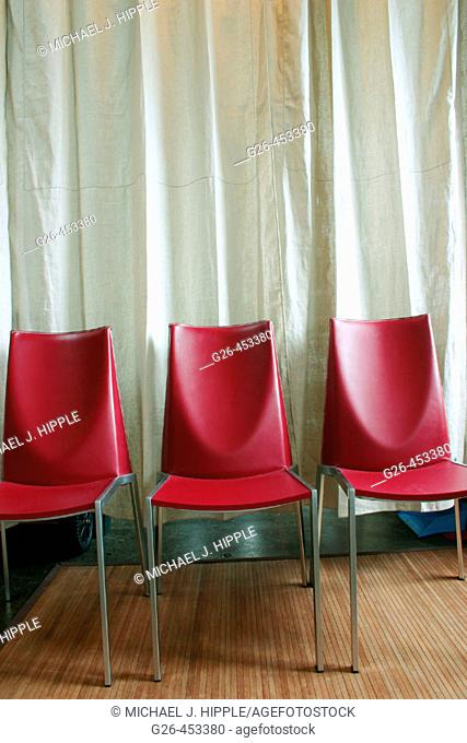 Row of red leather chairs against white curtain