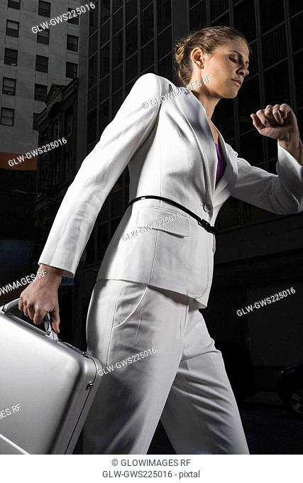 Low angle view of a businesswoman walking and checking the time