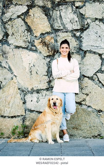 Portrait of a smiling young woman with her Golden retriever dog at a stone wall