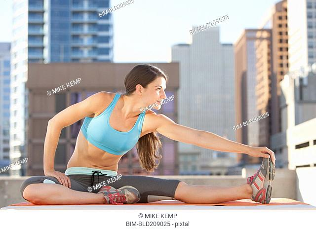 Caucasian woman stretching on urban rooftop