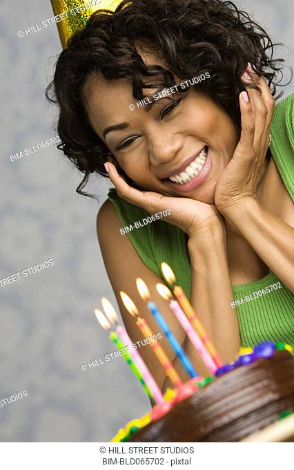 Surprised mixed race woman viewing birthday cake