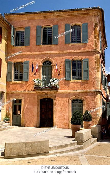 Roussillon. Exterior facade of building with typical ochre coloured walls and painted window shutters
