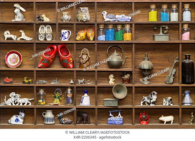 A collection of souvenirs and other curiosities displayed on a small hanging shelf