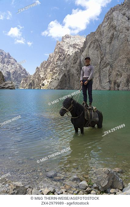 Kyrgyz showing his agility on his horse in Köl-Suu lake, Kurumduk valley, Naryn province, Kyrgyzstan, Central Asia