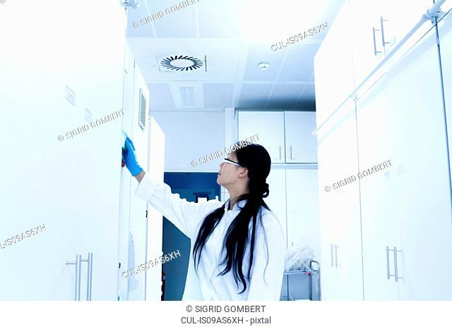 Female scientist opening sample cupboard in laboratory