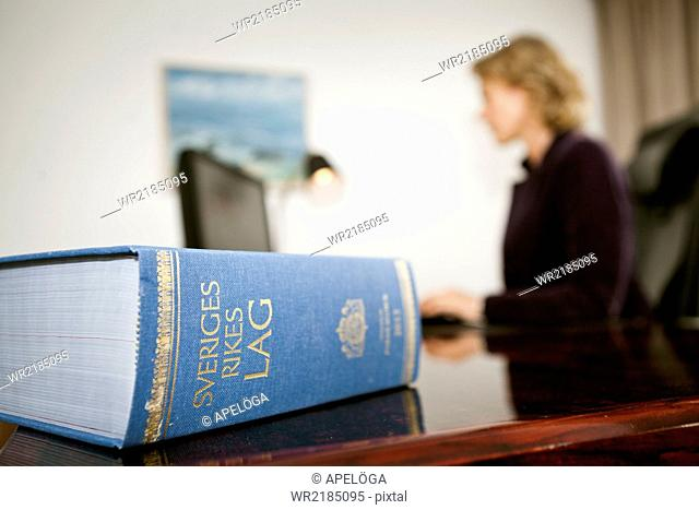 Swedish law book on table with female lawyer working in background