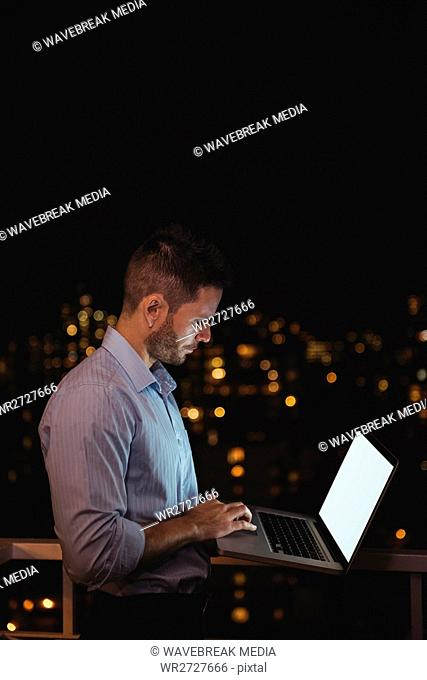 Man using laptop in the balcony