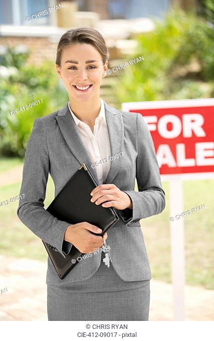 Portrait of smiling realtor near For Sale sign