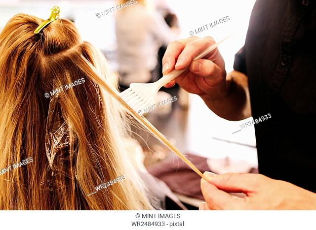 A hair colourist, a man using a paintbrush to cover sections of a woman's blonde hair