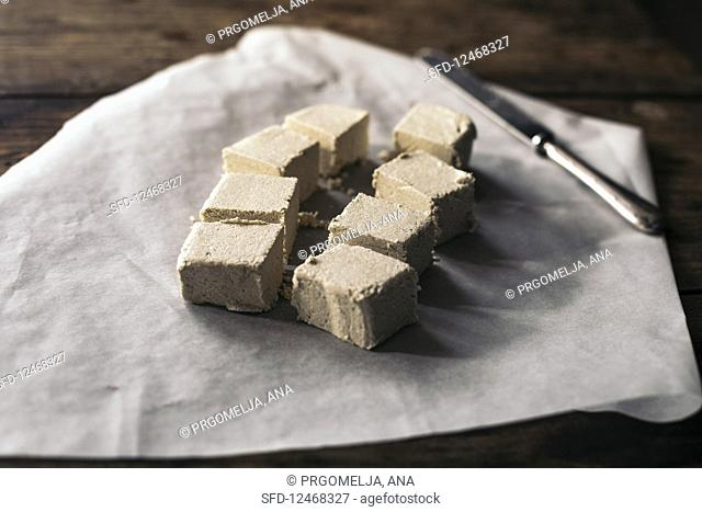 Diced halva on a piece of paper with a knife