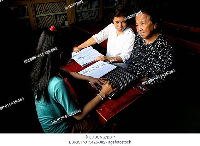 Vietnam. Center for blind children. Girl writing braille. Sister Elisabeth (Franciscan sisters) ensure the smooth running of the centre