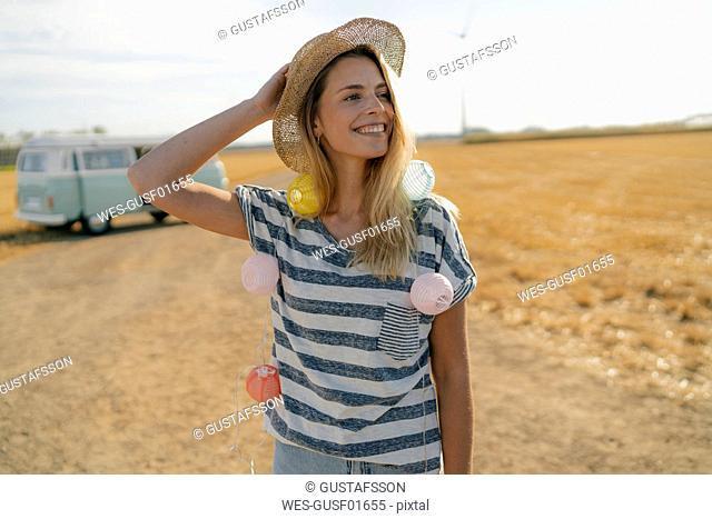 Happy young woman at camper van in rural landscape