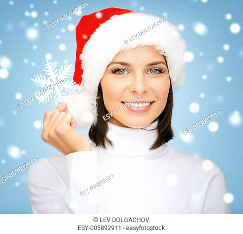 christmas, x-mas, winter, happiness concept - smiling woman in santa helper hat with big snowflake