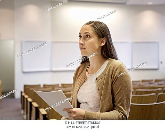 Female student holding essay in lecture hall
