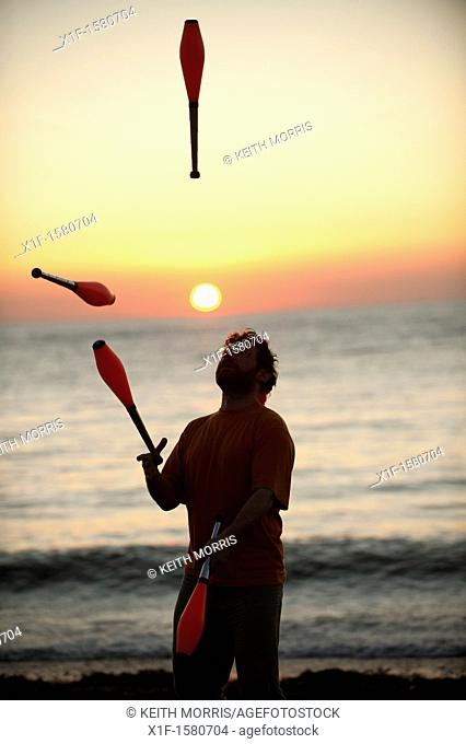 A man juggling at sunset on the beach on a very warm late september evening Aberystwyth Wales UK