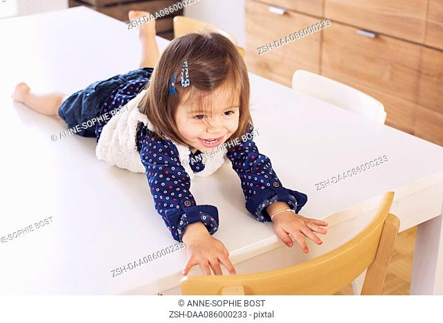 Little girl lying on top of table