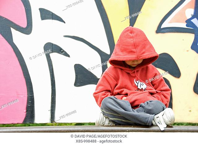 Stock photo of a young boy sitting cross legged in front of a wall covered with Graffiti
