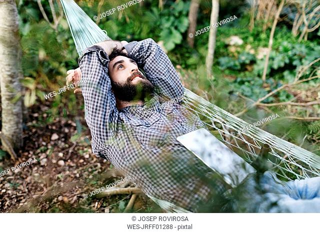 Man lying relaxed in hammock with a tablet