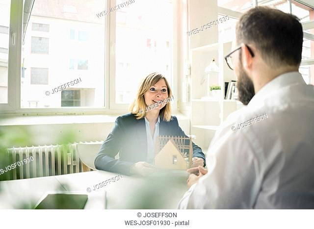 Woman with house model smiling at man in office