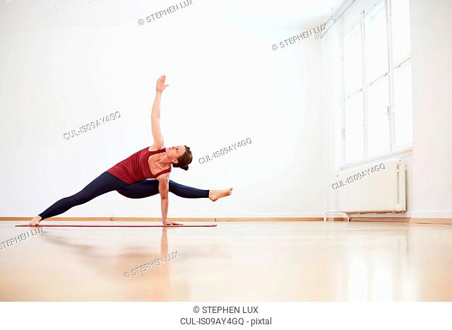 Woman in exercise studio arm and leg raised in yoga position