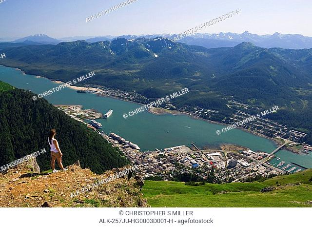A hiker takes in the view of Gastineau Channel, Douglas Island, and Downtown Juneau from the top of Mt. Juneau in Southeast Alaska during Summer