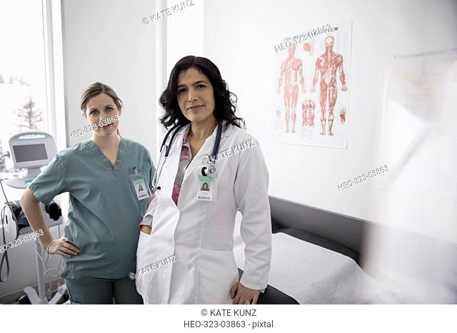 Portrait confident female doctor and pregnant nurse in clinic examination room