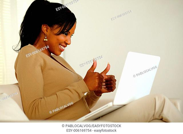 Portrait of a positive young woman looking to laptop screen while sitting on sofa at home indoor and lifting the fingers up