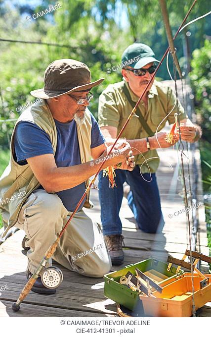 Active senior male friends preparing fishing lines