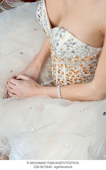 Close up of a young woman wearing a dress sitting down waiting