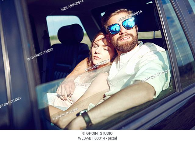 Affectionate young couple relaxing in car