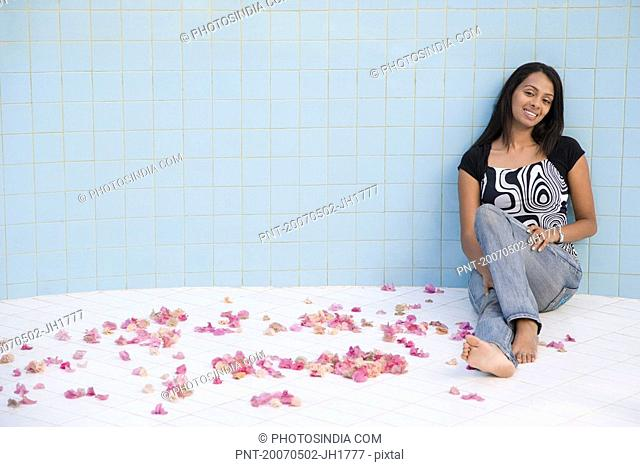 Portrait of a young woman smiling in an empty swimming pool