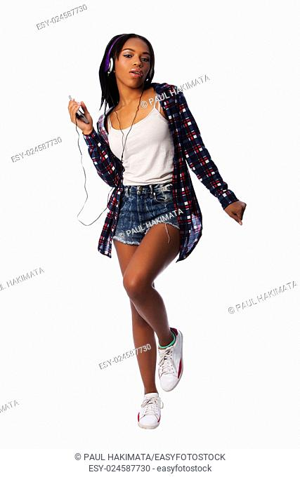 Beautiful teenager girl listening, dancing and jamming to music on mobile phone wearing purple headphones, on white