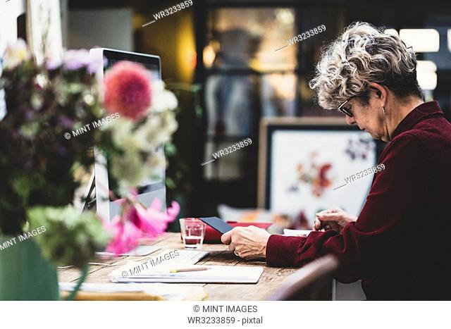 Senior woman wearing glasses and red dress sitting at a wooden table, looking at digital tablet