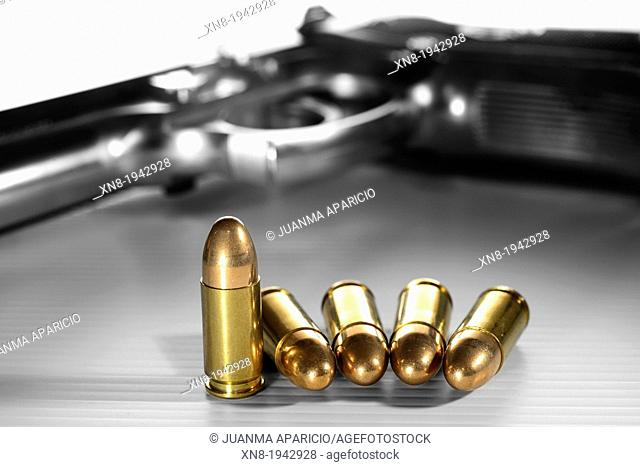9 mm Bullets at foreground and gun in B&W out of focus in background