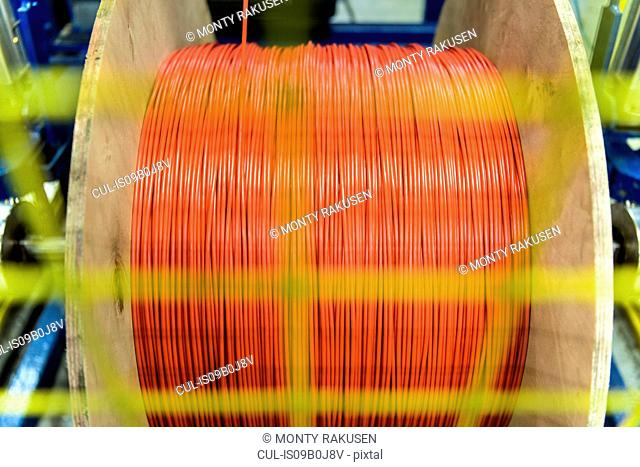 Red cable spinning on spool in cable factory